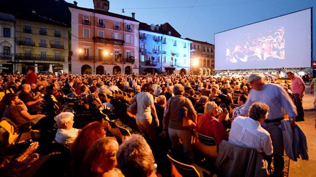 Auf der Piazza Grande in Locarno sitzen viele Menschen und schauen auf eine grosse Leinwand.
