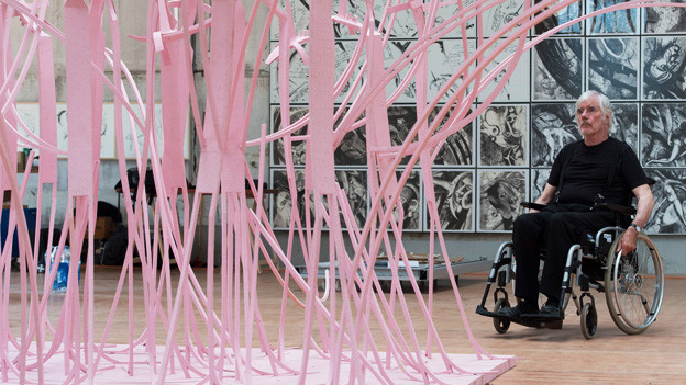 Schang Hutter sitzt im Rollstuhl und betrachtet eine seiner rosa angemalten Figurengruppen.