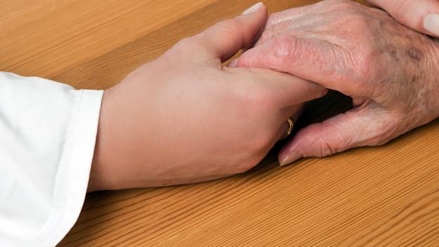 Zwei junge Hände halten eine ältere Hand.