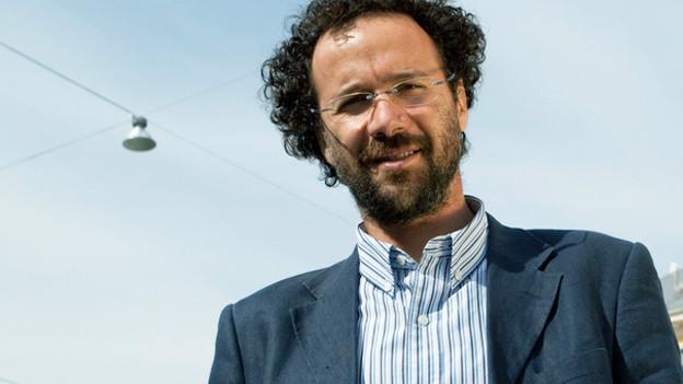 Ein Mann mit dunklen Locken und Brille schaut von oben herab in die Kamera.