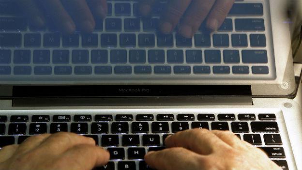 Ein Computer und Hände darauf.