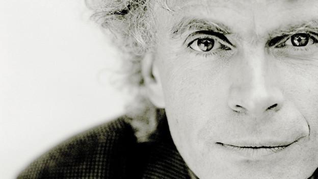 Das Closeup eines Mannes mit grauen Locken.