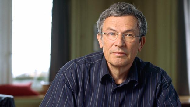 Das Porträt eines Mannes mit Brille und grau mellierten Haaren.