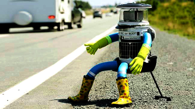 Roboter sitzt am Strassenrand.