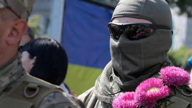 Ein vermummter Soldat hält rosa Blumen.