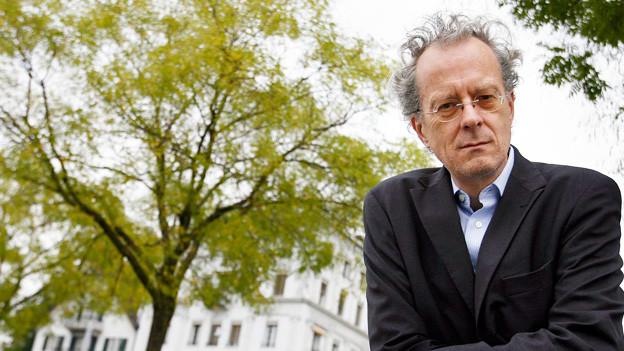 Ein Mann mit grauen Haaren und Brille steht vor einem grünen Baum.