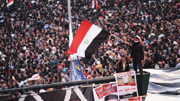 Eine vermummte Person hält eine Fahne. Im Hintergrund eine Menschenmenge.