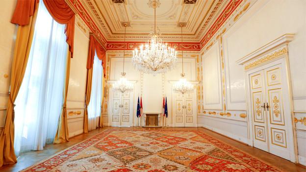 Ein prunkvoll ausgestatteter Saal von innen, mit hohen Fenstern, Kronleuchtern und goldenen Dekorationen.