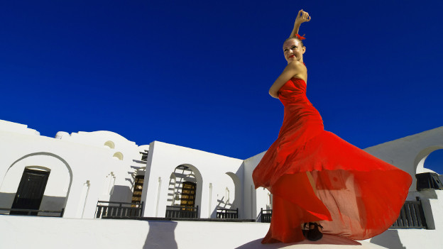 Frau tanzt Flamenco vor blauem Himmel.