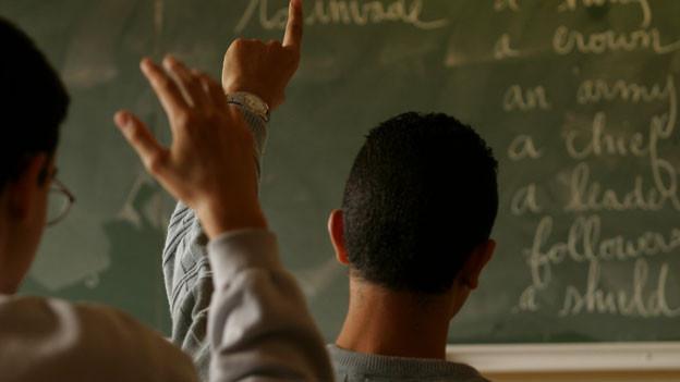 Ein Schüler streckt auf. Man sieht auf eine Tafel mit Englisch-Vokabeln.