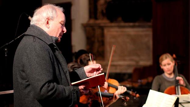 Christopher Hogwood dirigiert mit einem Buch in der Hand.