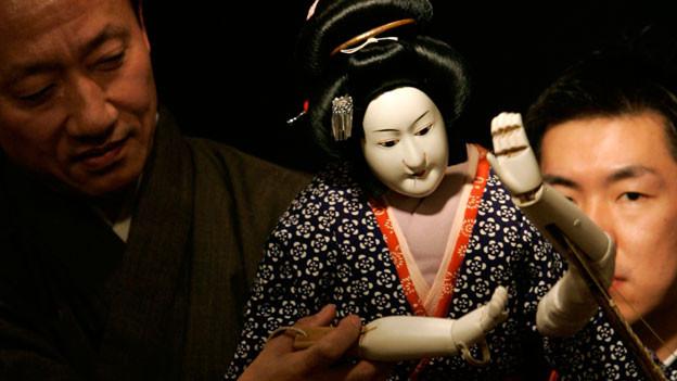 Eine Bunraku -Puppe und zwei Männer im Hintergrund.