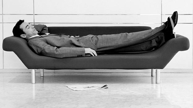 Mann liegt auf Sofa.