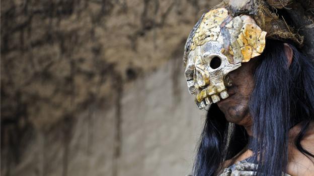 Ein Schamane mit einer Totenschädel-Maske.