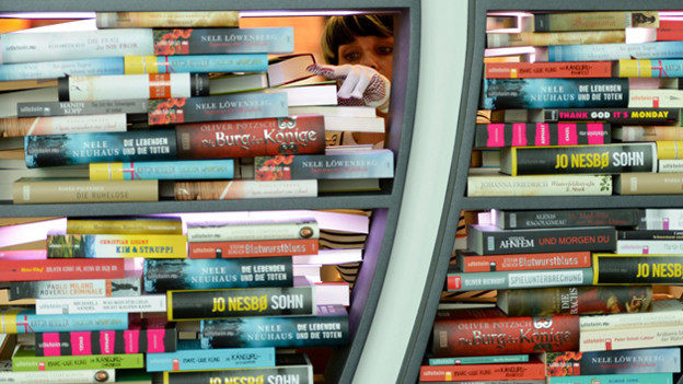 Frau füllt ein Bücherregal auf.