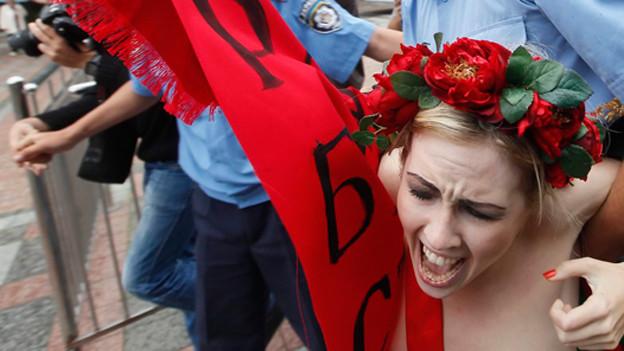 Eine Frau mit nacktem Oberkörper wird von Polizisten festgehalten.