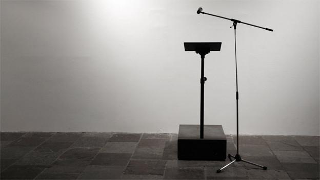 Ein Rednerpult und ein Mikrofon stehen auf Steinboden.