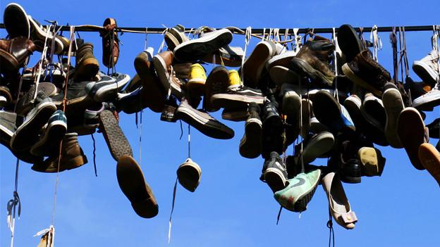 Schuhe hängen an einer Leine.