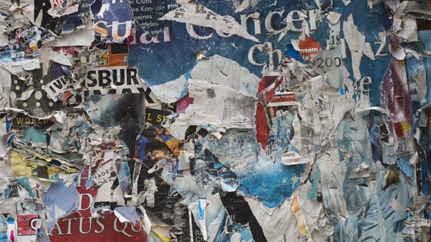 Gerissene Poster hängen in Berlin an einer Mauer.