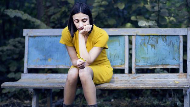 Eine Frau mit gelbem Kleid sitzt auf einer Bank mit ihrem Handy in der Hand.