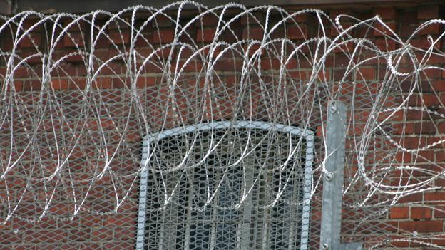 Ein Gefängnisfenster mit Zaun und Natodraht.