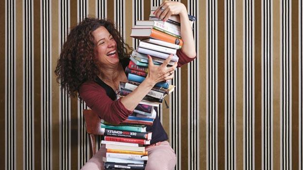 Eine Frau lacht und hält einen Stapel Bücher.