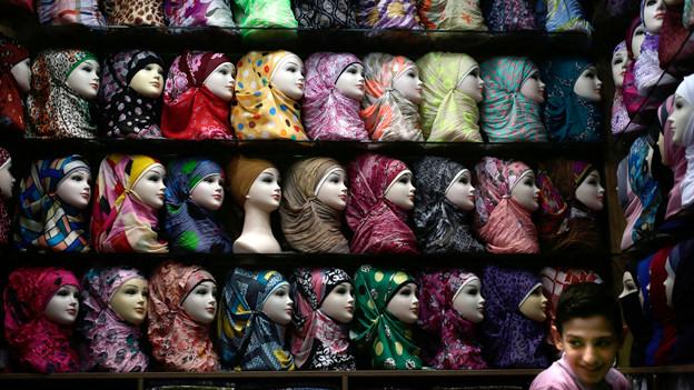 Auf vielen Regalen stehen Schaufensterpuppenköpfe mit verschiedenen bunten Kopftüchern.