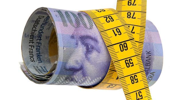 Ein Massband um eine Rolle Geldnoten