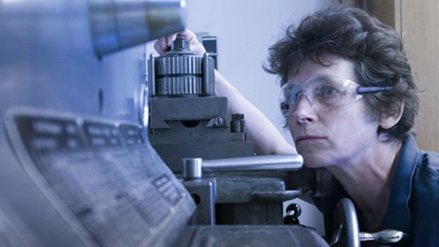 Eine Frau an einer Maschine.