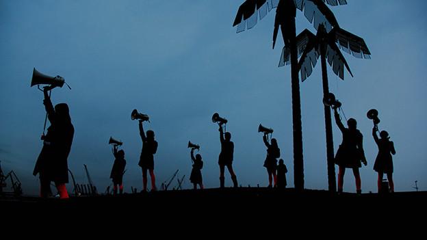 Silhouetten von Menschen, die auf einer Bühne Megaphone in die Höhe strecken.