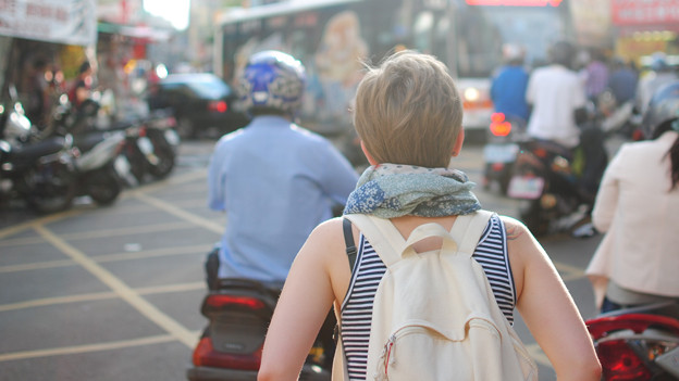 Eine Frau von hinten mit Rucksack.