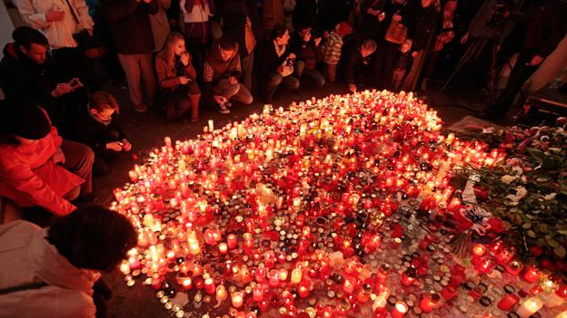 Menschen vor zahlreichen roten Kerzen.