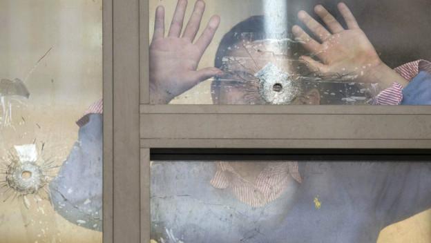Junge schaut durch ein Schussloch in einer Fensterscheibe.