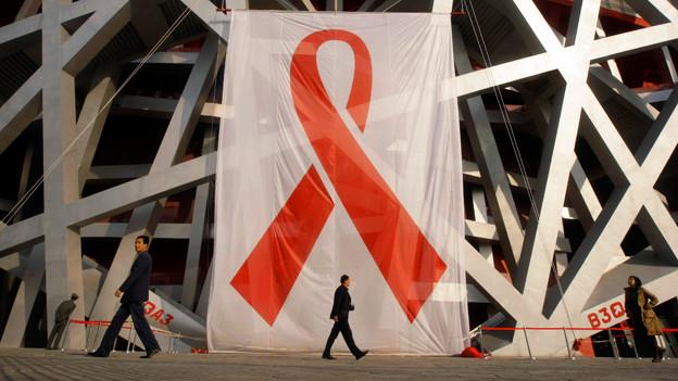 Ein Banner mit einem roten Band hängt an einem Gebäude.