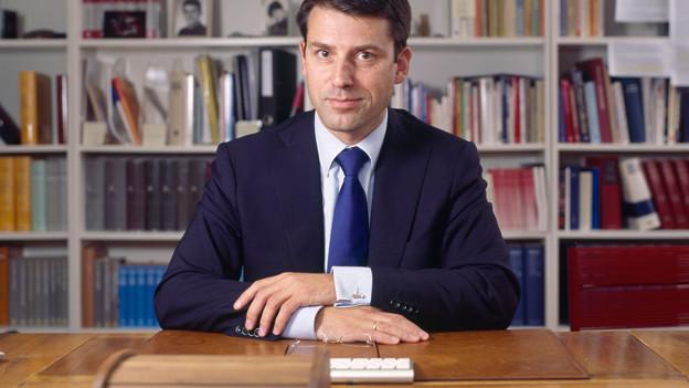 Porträt von Gottfried Locher am Schreibtisch.