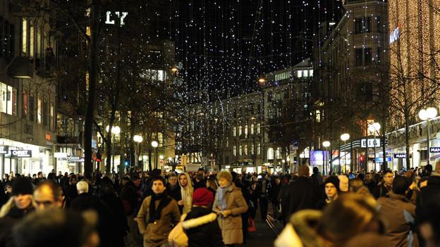 Die Zürcher Bahnhofstrasse mit vielen Leuten und Weihnachtsbeleuchtung