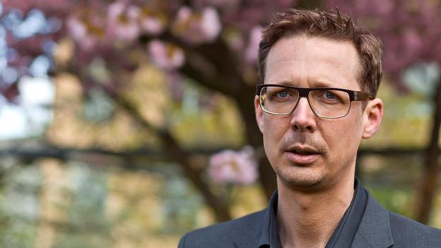Michael Hermann vor einem Baum.