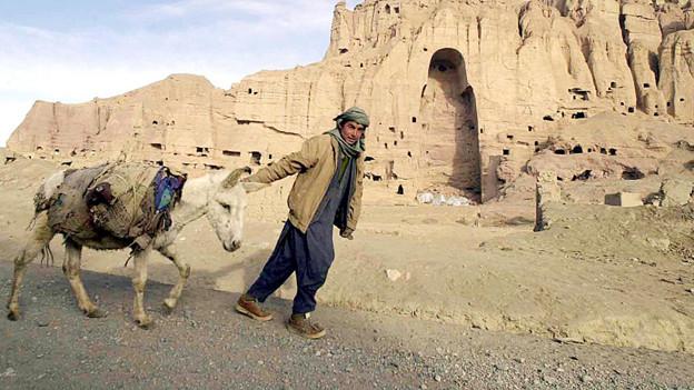 Ein Junge und ein Esel vor einem Berg mit zahlreichen Hühlen und einer riesigen, Vertiefung, die schemenhafte die Umrisse eines Menschen zeigt.