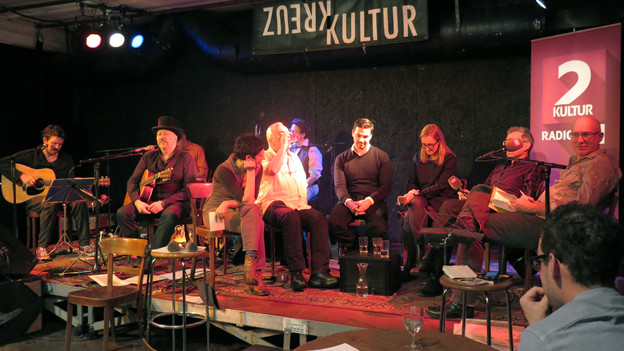 Leute führen eine Diskussion auf einer Bühne.