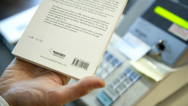 Hand mit Buch vor einer Kasse.