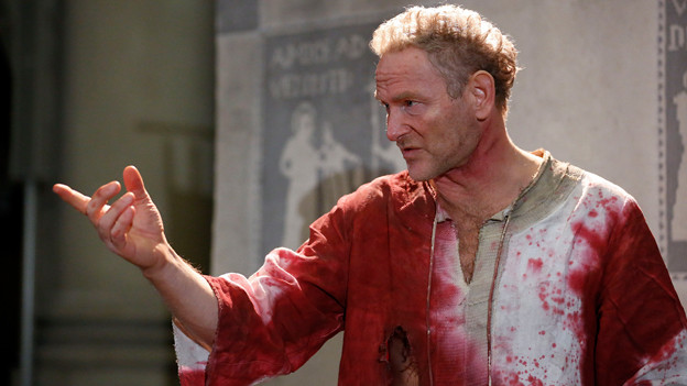 Ein Mann mit blutverschmiertem Hemd auf einer Bühne