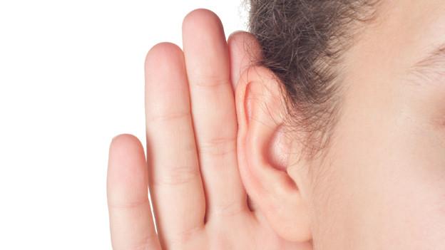 Ein Ohr mit einer angelehnten Hand