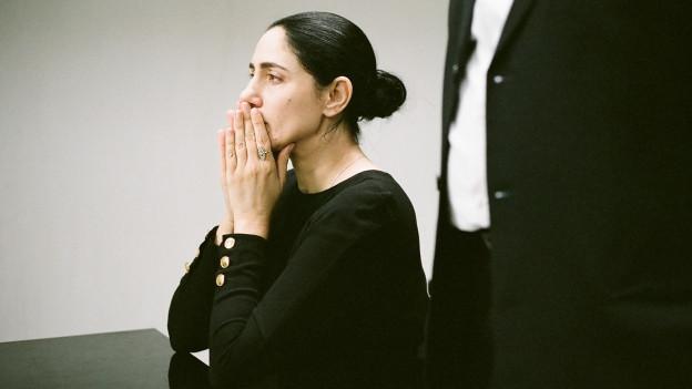 Frau hält die Hände vor dem Mund.