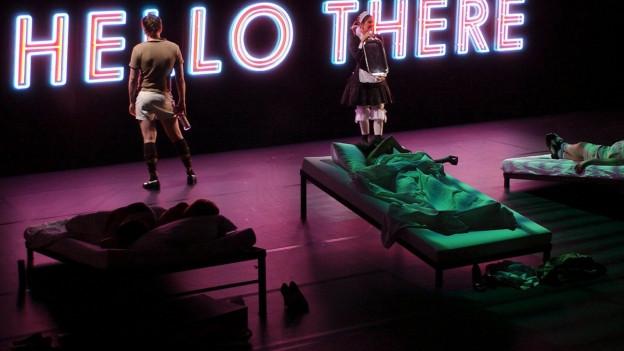 Eine von Neonlicht schwach beleuchtete Theaterbühne mit mehreren Feldbetten, in denen Kranke liegen. Eine Krankenschwester und ein Mann stehen im Hintergrund.