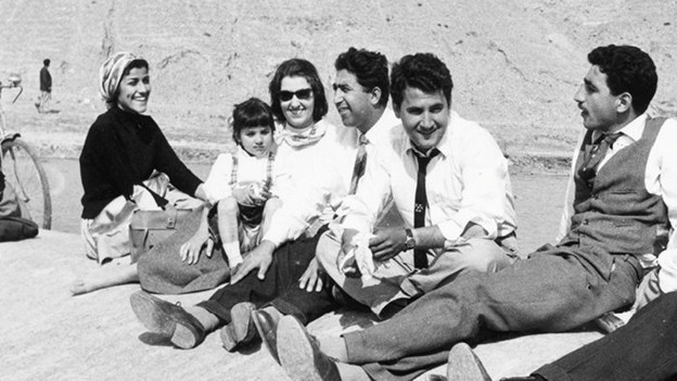 Schwarz-Weiss-Aufnahme: Eine Gruppe von Menschen sitzt vergnügt an einem See.