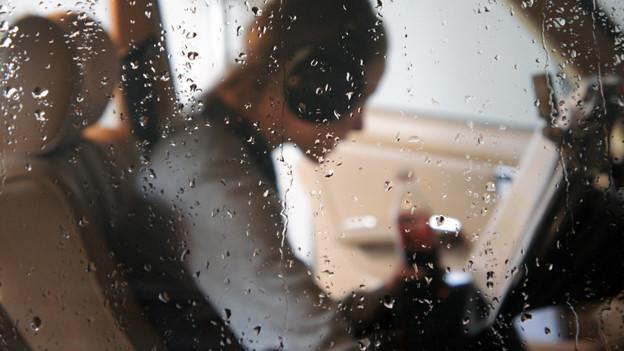 Mann sitzt hinter regennassen Scheiben und hört Musik.