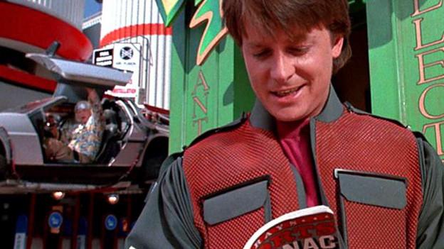 Michael J. Fox liest in seiner Rolle als Marty McFly in einem Football-Almanach, während Christopher Lloyd als Dr. Brown mit seinem zur Zeitmaschine umgebauten DeLorean-Sportwagen ankommt.