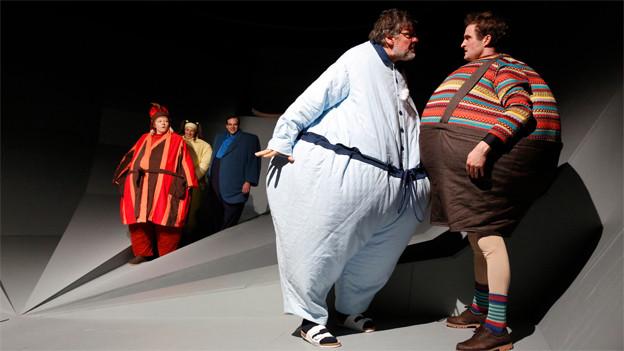 Menschen in dicken Kostümen, mit kugelrunden Bäuchen, auf einer Bühne.