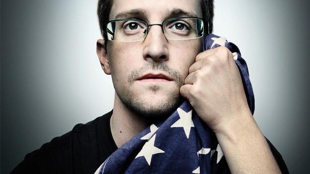 Porträt von Edward Snowden, wie er eine Flagge der Vereinigten Staaten mit der Hand an sein Gesicht hält.