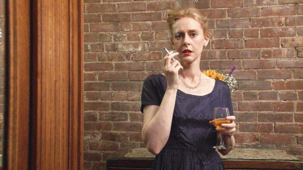 Eine Frau im dunkelblauen Kleid trägt ein Weinglas und raucht.
